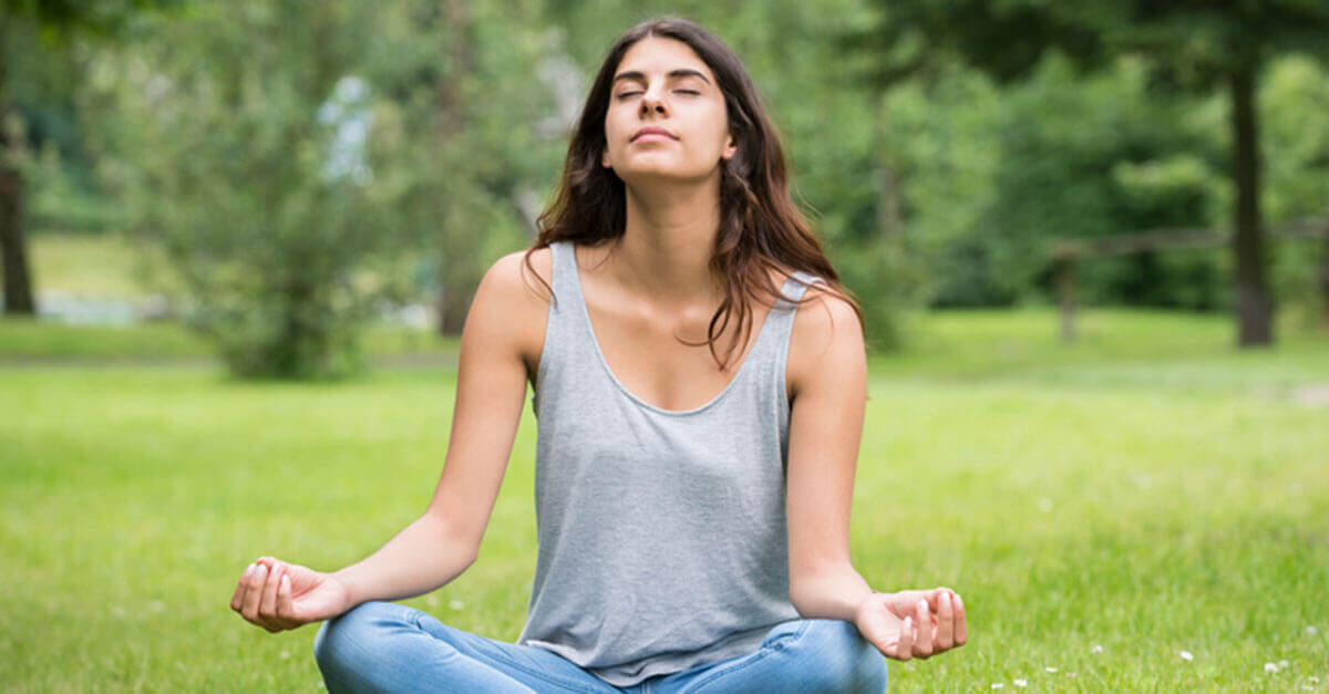 Woman sitting outside meditating and relaxing