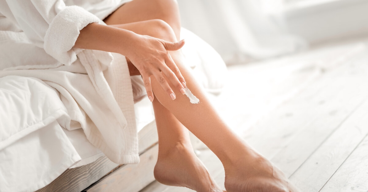 Woman applying white cream to leg