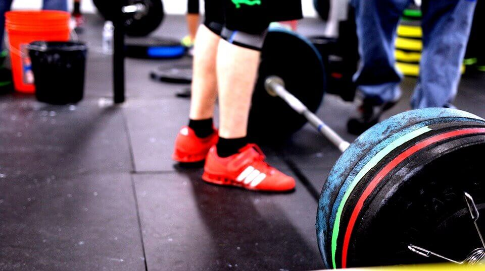 working out in the gym with barbell weights and red shoes