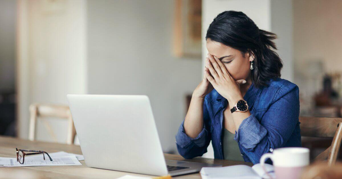 woman at a computer looking stressed