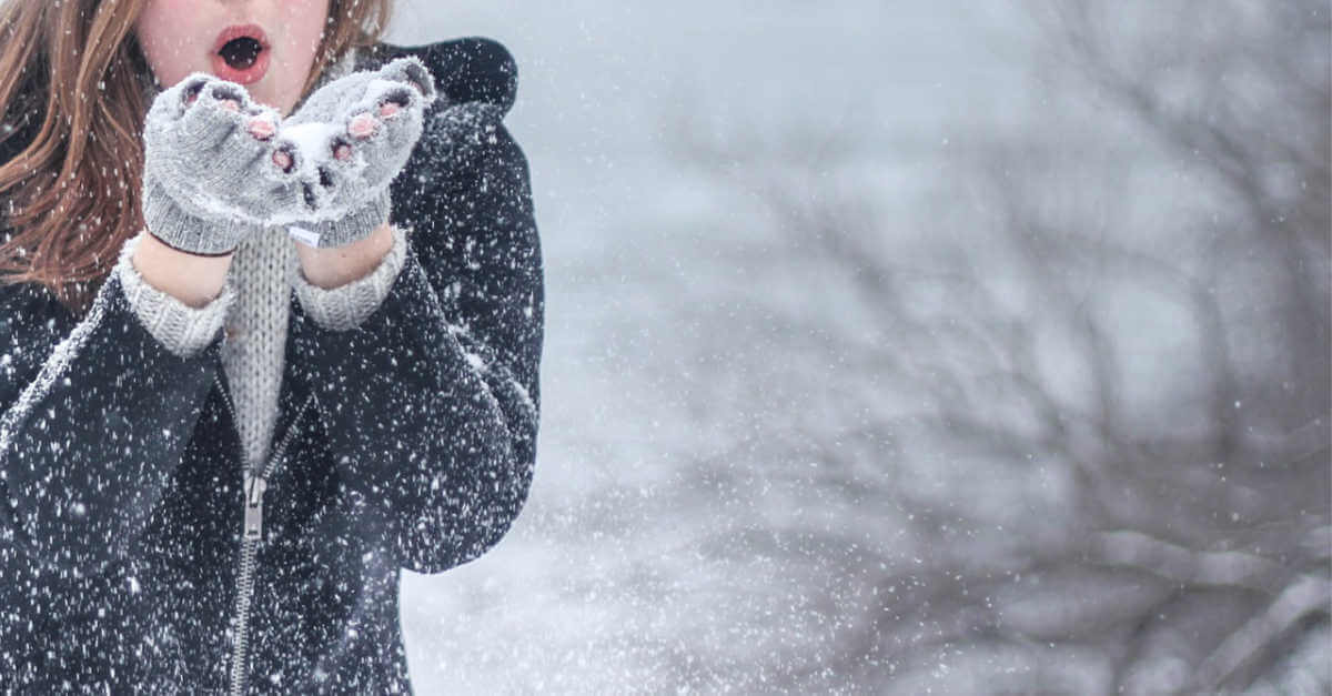 a woman with snow and gloves, caring for winter skin
