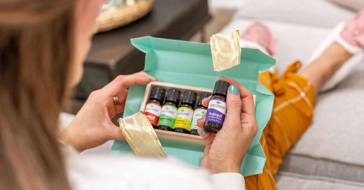a woman opening a gift with Plant Therapy essential oils