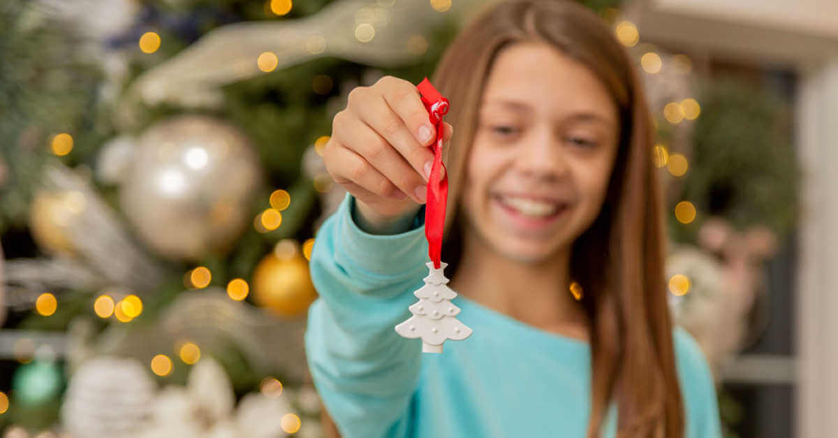 girl holding a christmas ornament for essential oil diffusion