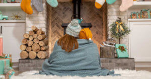 Mother and son cuddled by fireplace during Christmas