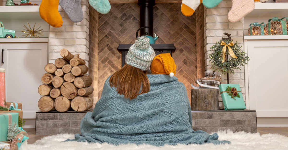 Mother and son cuddled by fireplace during Christmas winter skin