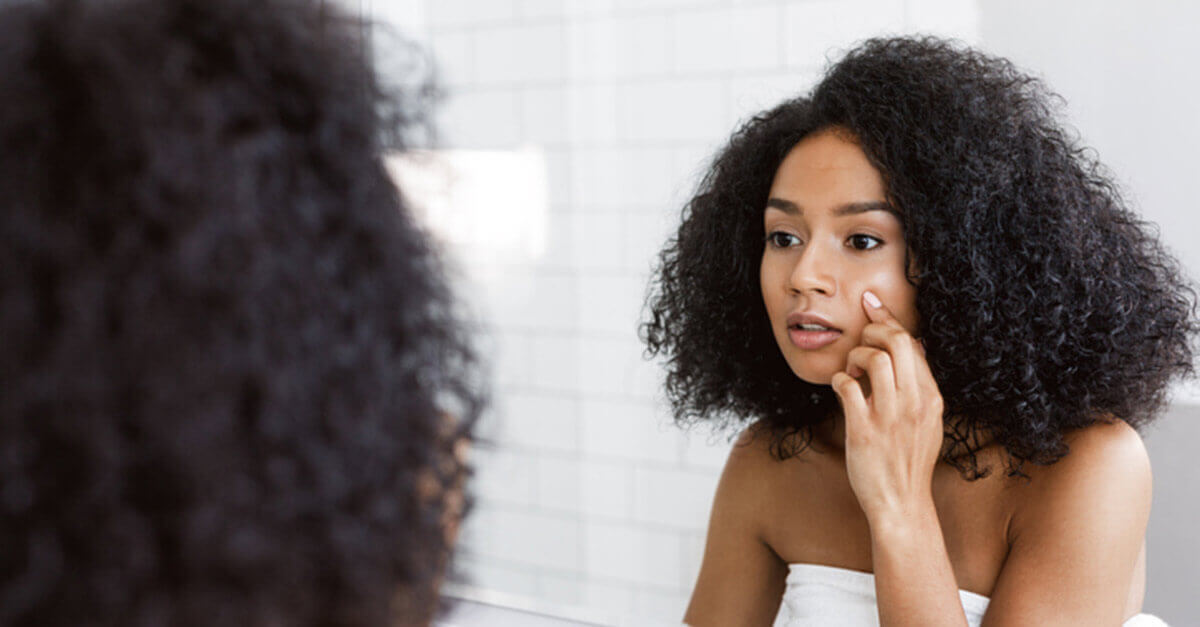 Woman looking at herself in the mirror and touching her face