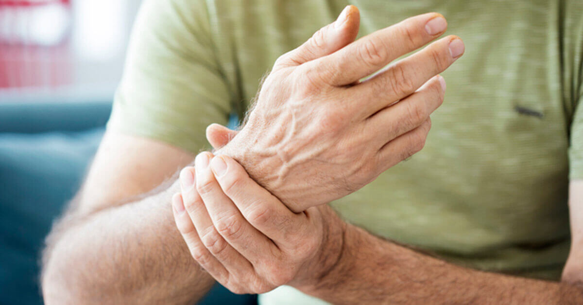 Man holding wrist in pain or discomfort from joints or muscles