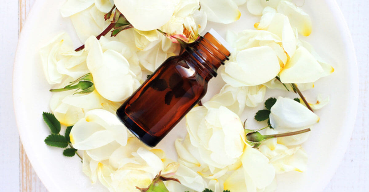 Essential oil bottle in a bowl of white roses