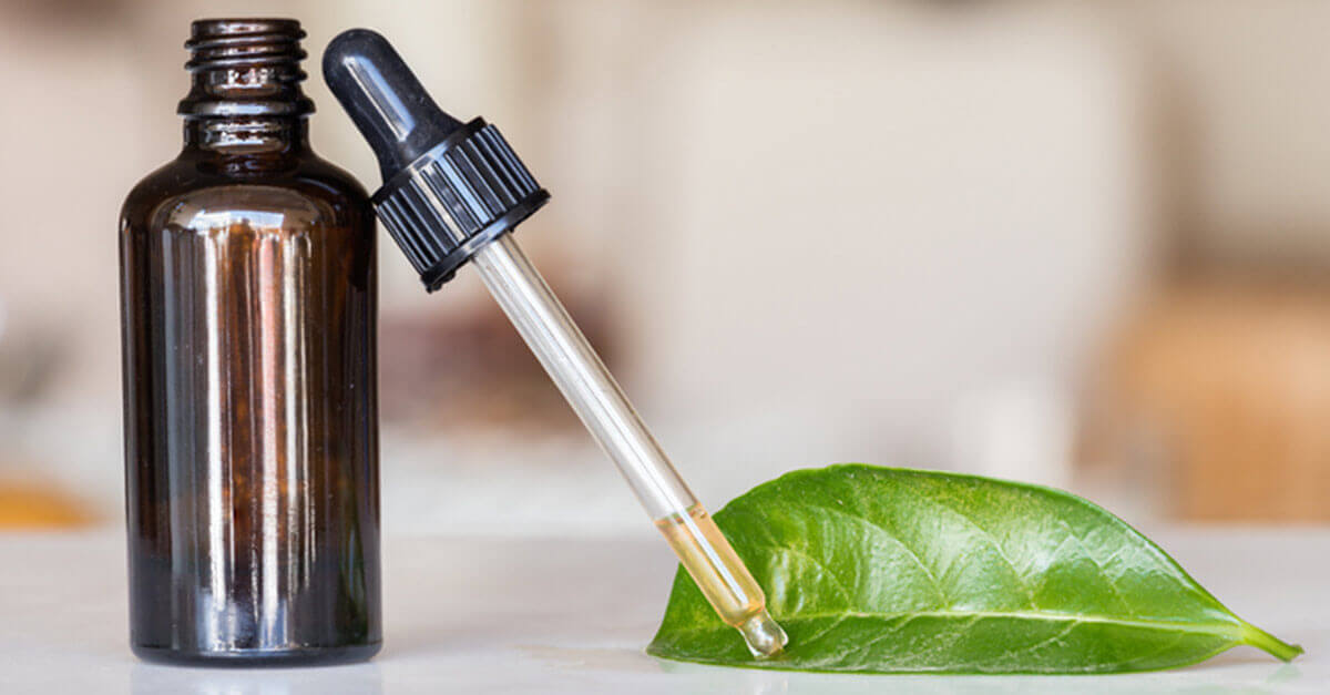 Essential oil bottle with dropper and green leaf
