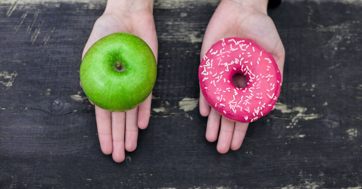 hand holding doughnut and apple, choosing between healthy food and junk food