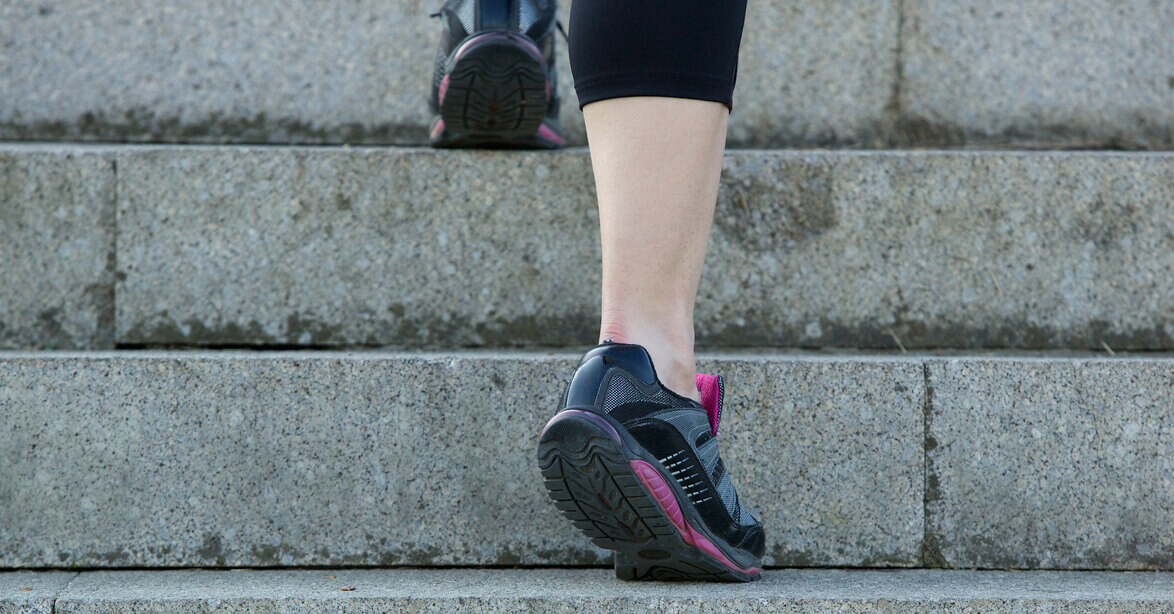 woman walking up stairs in gym shoes
