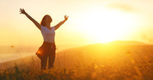 Happy woman holding arms out in sunny yellow field