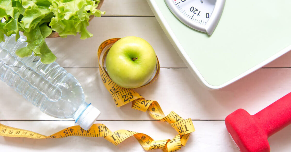 ingredients for weight loss, tape measure, apple, weights, and apple