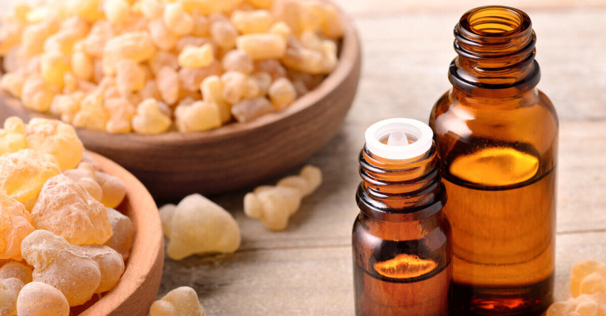 Frankincense resin in bowls with full essential oil bottles