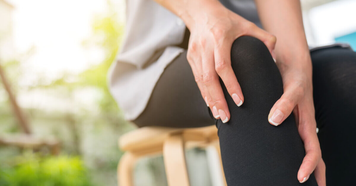 woman holding leg for muscular or joint discomfort