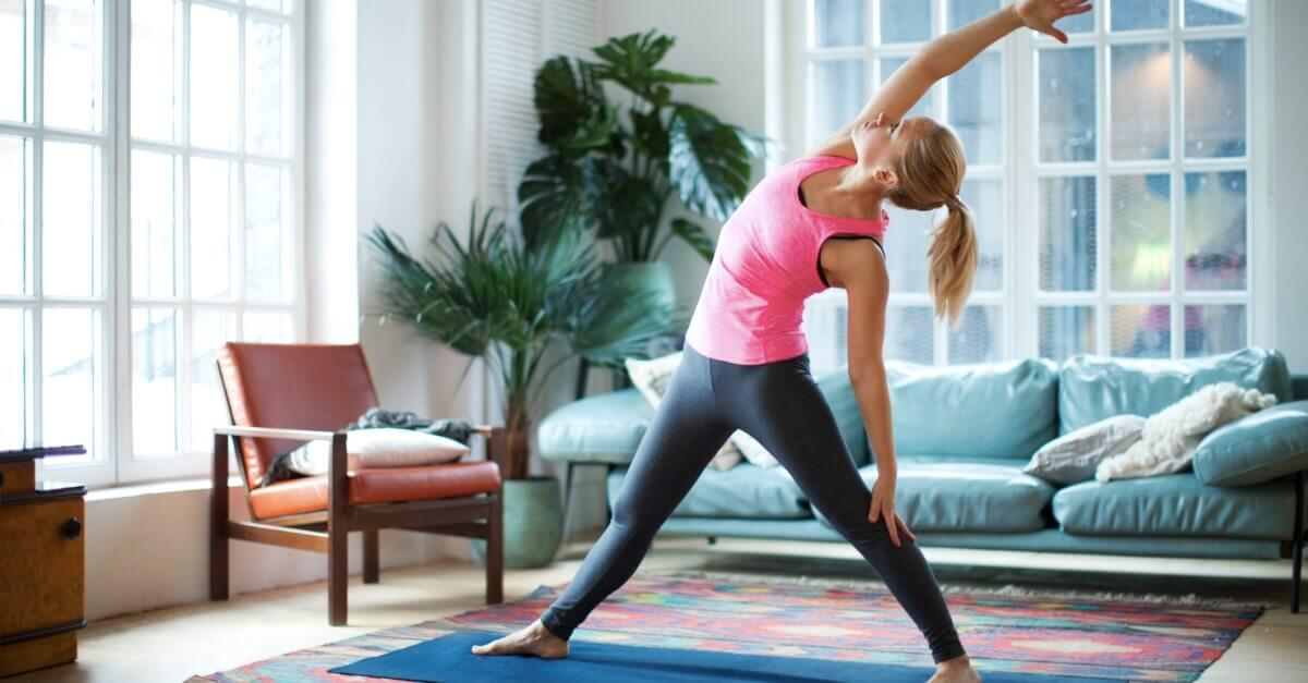 Woman stretching on her yoga mat at home