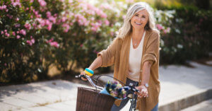 Older woman riding bike happily outdoors with pink roses in the background