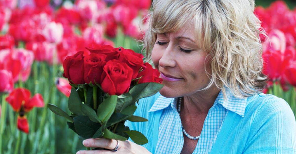 Woman smelling a bouquet of red roses in a flower field