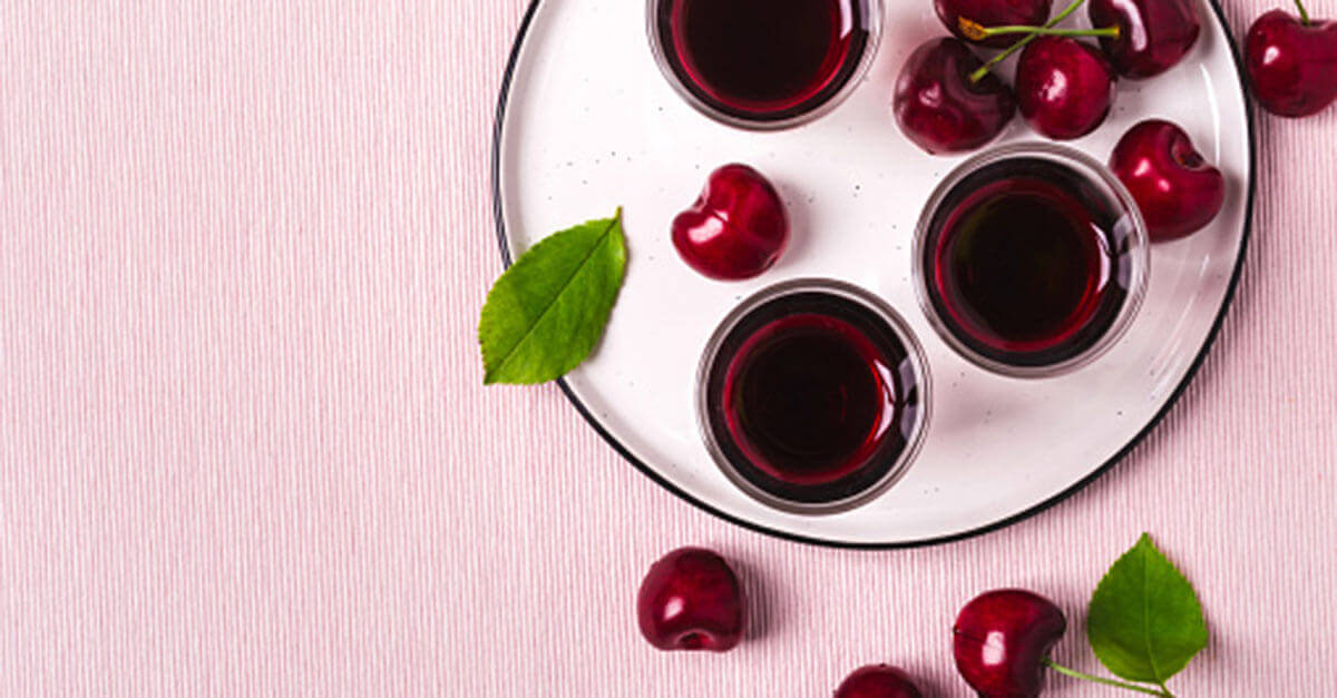 Cherrys with a red syrup on a pink background