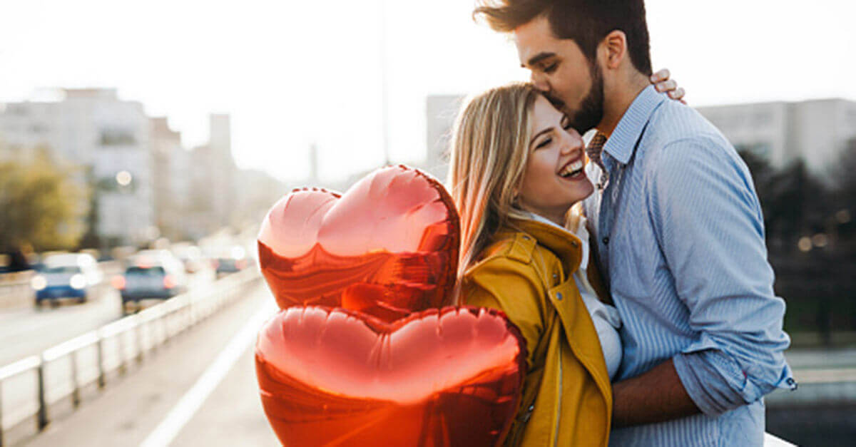 Man and woman hugging with red heart balloons
