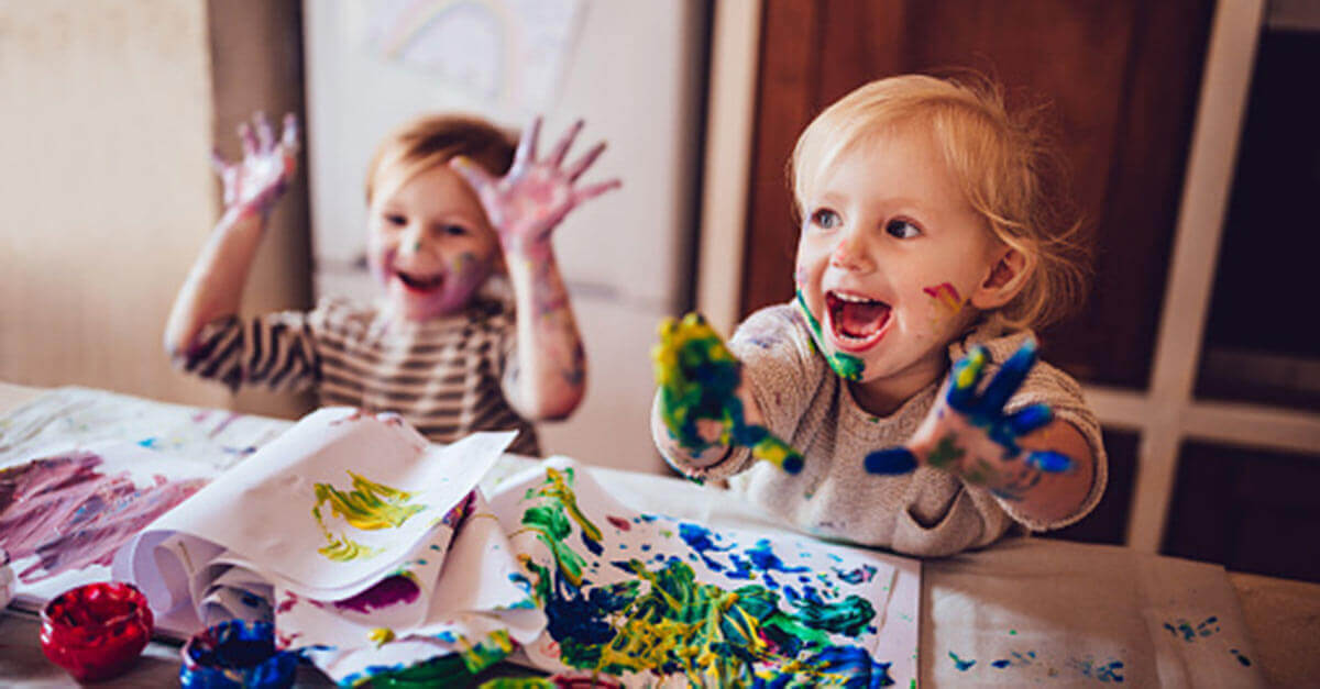 Young children making a mess with paints