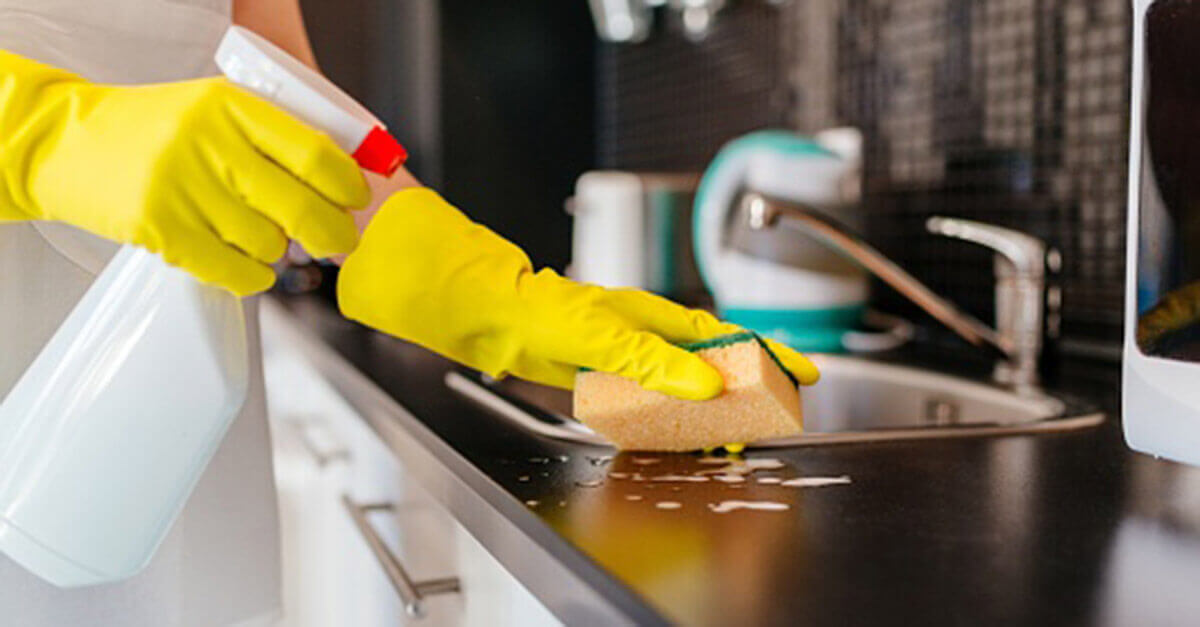 Yellow gloved hands spraying the kitchen counter