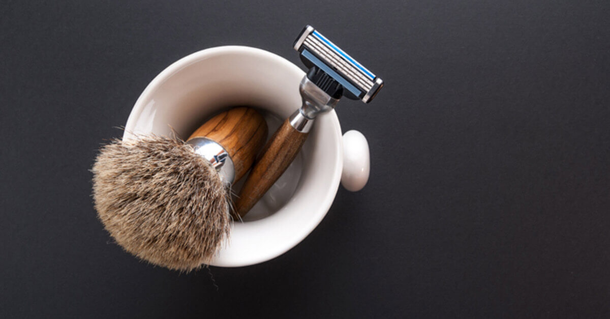 men's shaving products with razor and brush in a white mug