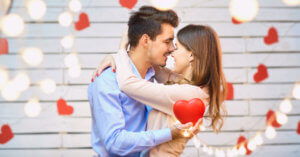 Young man and woman hugging with red heart decorations and lights around