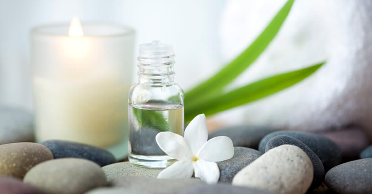 Clear essential oil bottle next to a jasmine flower and candle