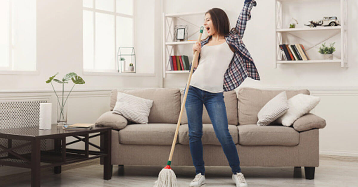 Woman dancing in her clean living room with a mop