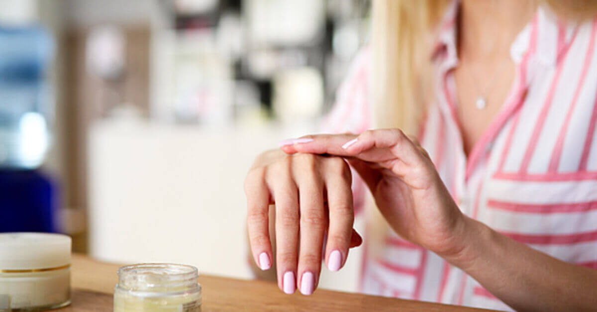 Woman's hand rubbing lotion on other hand