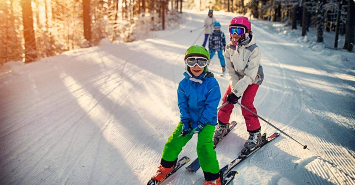 Children skiing in the snow with family