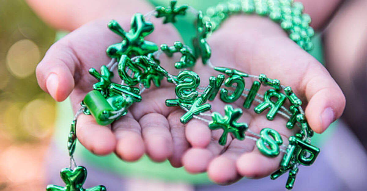 Hands holding green St. Patrick's Day necklace