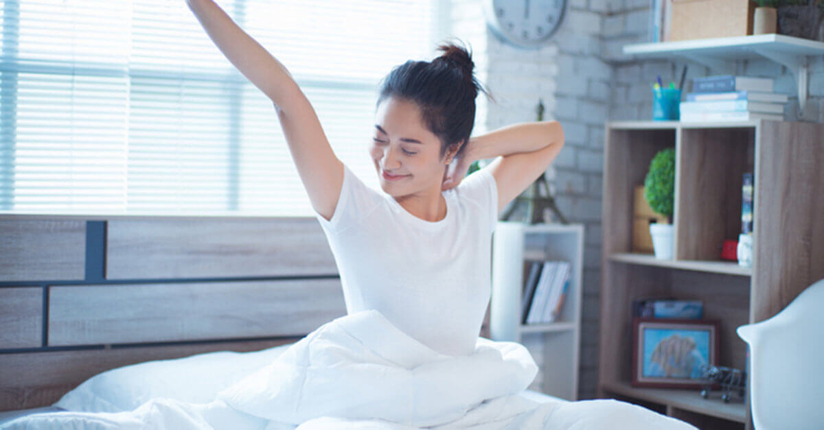 Woman waking up refreshed in her bed after sleep