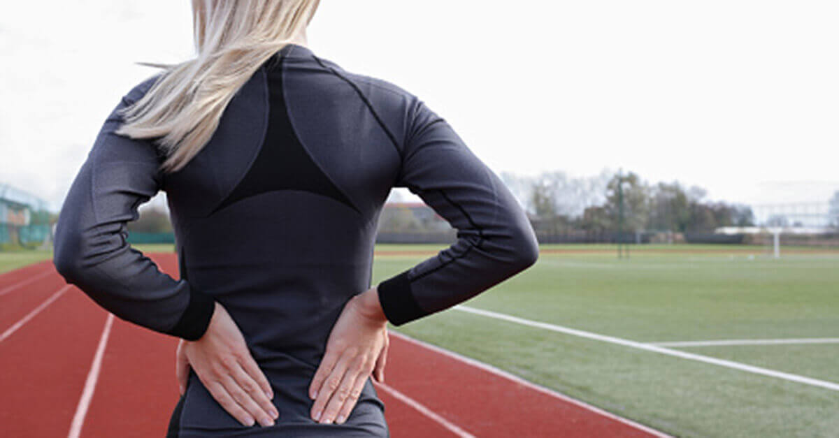 Woman holding her lower back on a running track