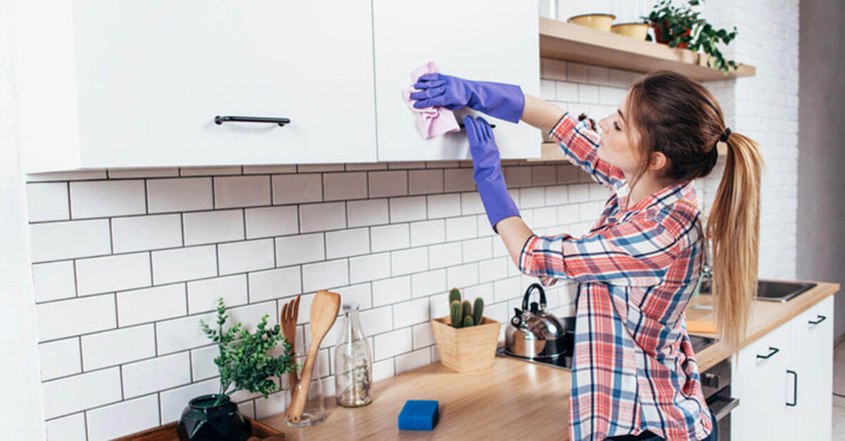 Woman cleaning her kitchen cupboards