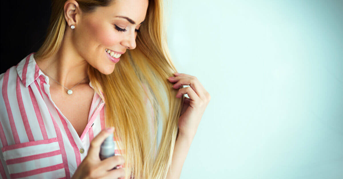Woman spraying product on her hair