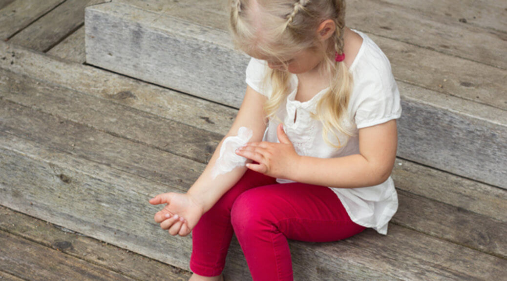child with cream on her itchy arm