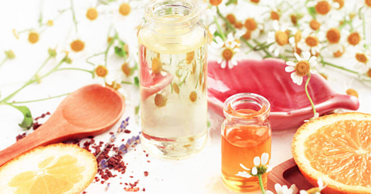 Essential oil bottles next to orange slices and flowers