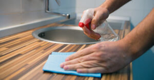 Hand cleaning a counter using a spray bottle