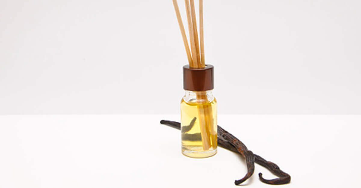 Vanilla beans next to an essential oil bottle filled with diffuser reeds