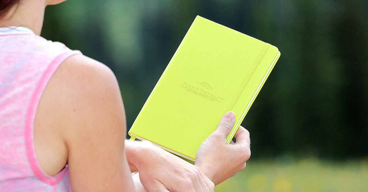 A woman holding the Essential Oil Journal and Organizer from Plant Therapy