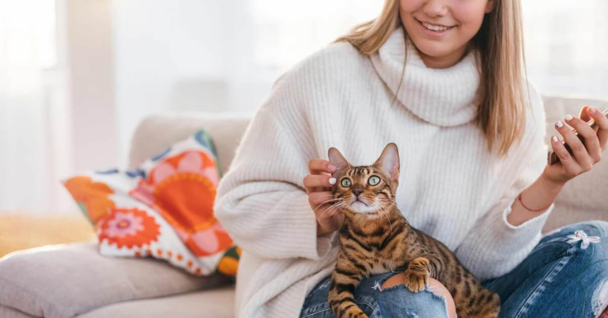 Woman petting her cat at home