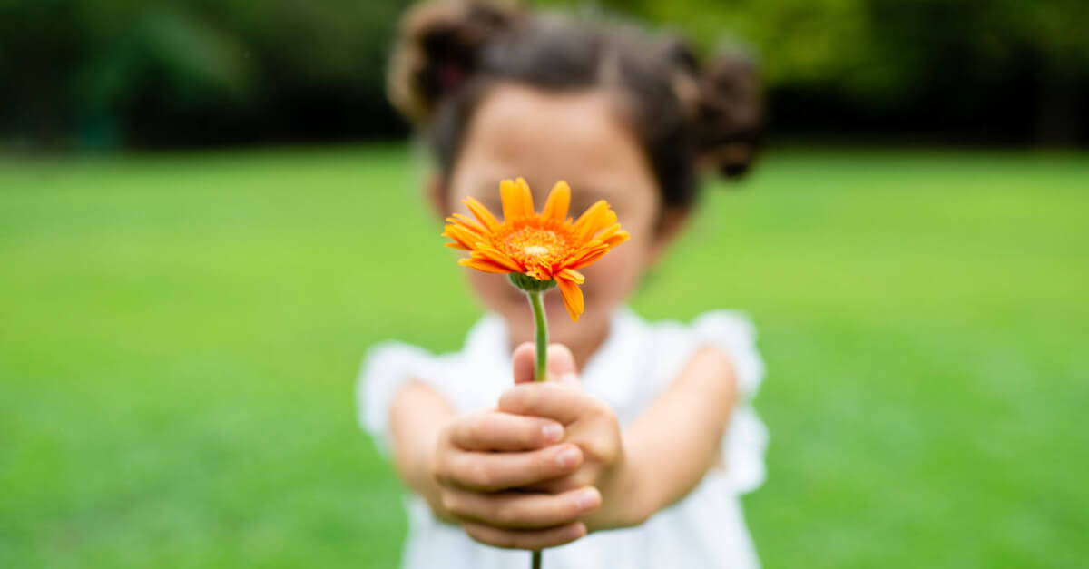 Young girl holding out an orange flower