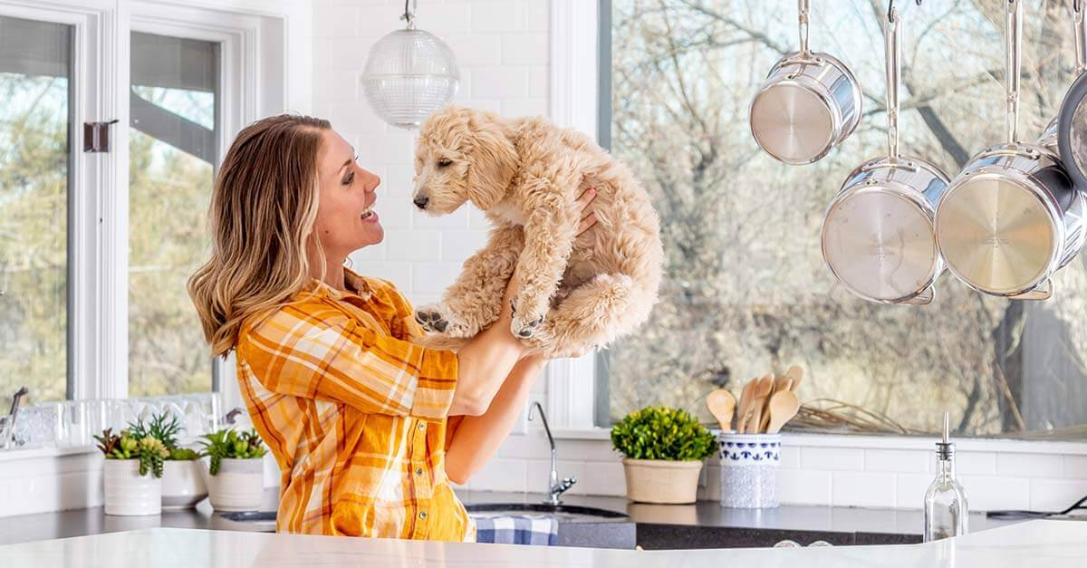 Woman holding up her pet dog