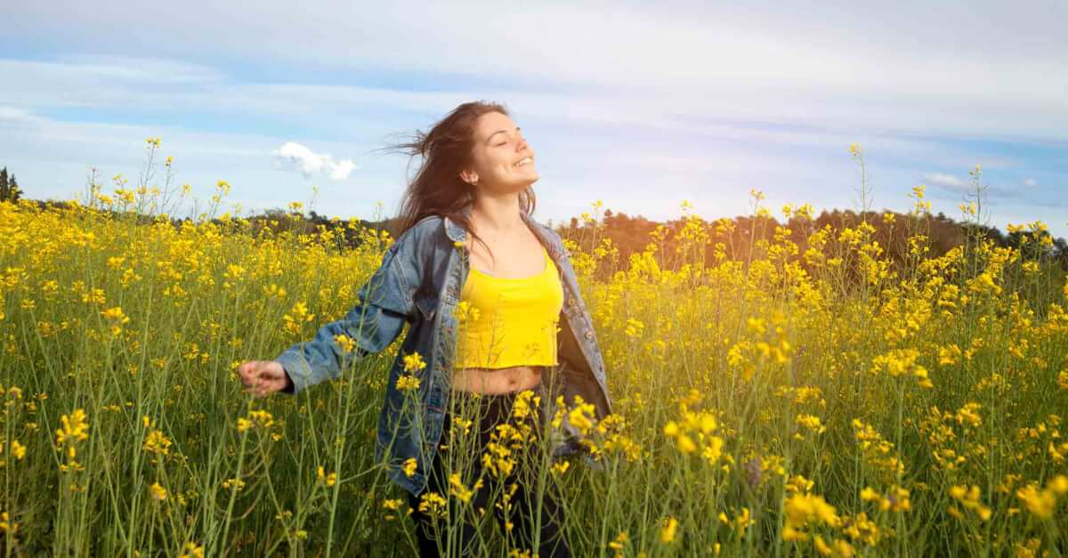 woman in a field breathing deeply