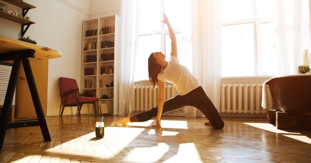 Woman doing yoga, self-care in her living room