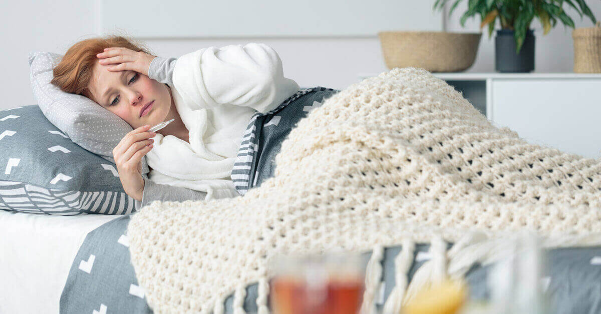 woman lying on the couch feeling sick