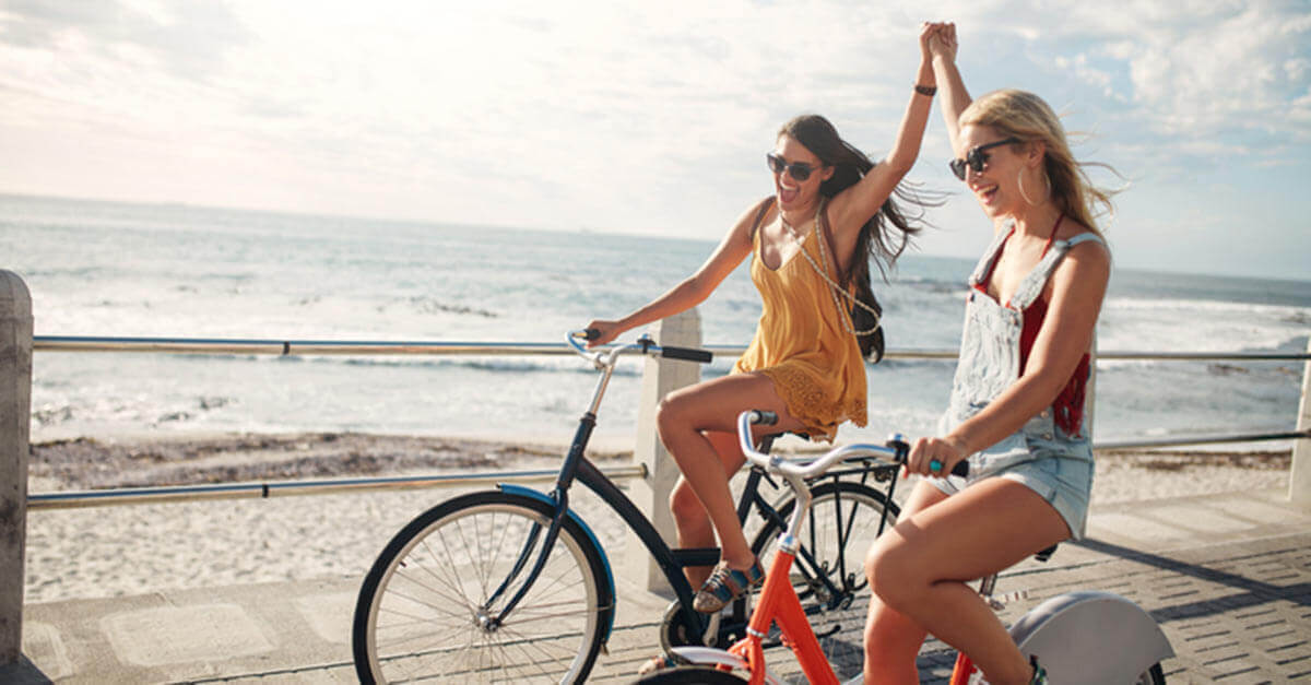 Two friends riding their bikes on a beach