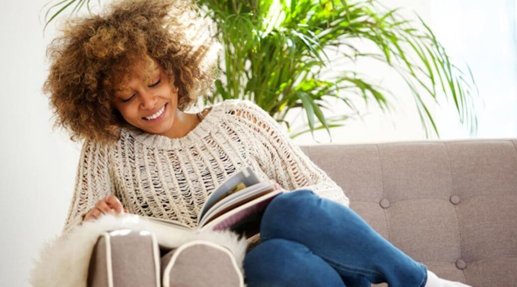 Woman sitting on her couch reading